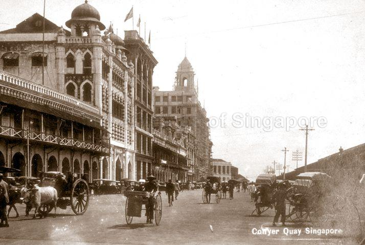 Collyer Quay with view of Alkaff Arcade (building with onion domes), the Union building (background) under construction and the Exchange Building (Fullerton Building) at the far end. Source: National Archives