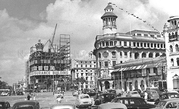 View of Ocean Building (right) and Asia Insurance Building (left) under construction at Collyer Quay, Singapore. Buildings were decorated to celebrate the coronation of Queen Elizabeth II.