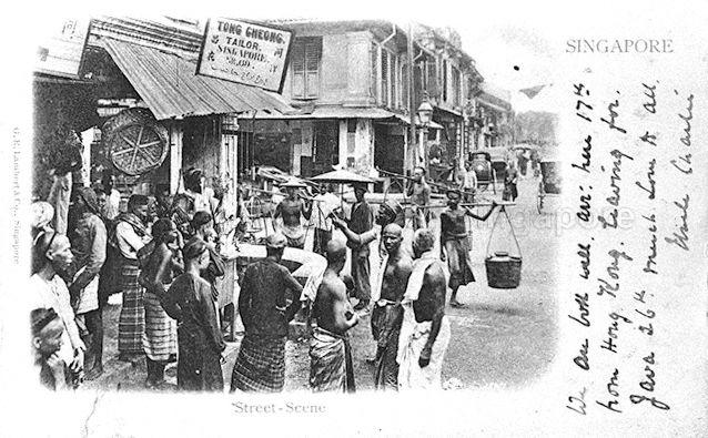 A gathering of street hawkers and others in front of Tong Cheong Tailor at the junction of South Bridge Road and Cross Street in Chinatown, Singapore. Cross Street was a busy street in the city popular for its many street shows and shops. Although in Chinatown, the district between Cross Street and the nearby Chulia Street was home to a substantial Indian community. The image reflects the multi-ethnic nature of Singapore society.