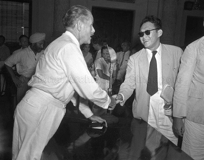 Singapore lawyer Lee Kuan Yew, counsel for Singapore Post and Telegraph Uniformed Staff Union, exchanging handshakes with Director of Posts, Singapore W A Cooper at the end of the arbitration proceedings between postal workers and the Government. The arbitrator from Kuala Lumpur, Yong Pung How, had awarded the workers 28 months' back pay.