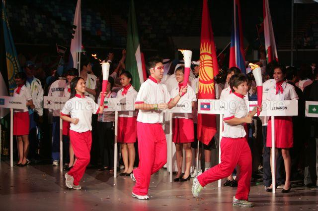 Torch bearers, from right, Olympic swimming finalist Tao Li …
