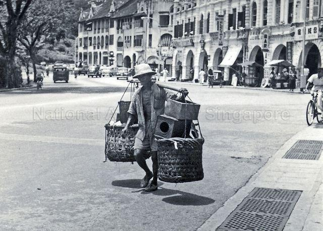 A street hawker at Bras Basah road in the 1950s. Amber Mansions located at the junction of Penang Road and Orchard Road is in the background.