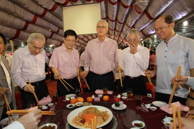 (From left) Grassroots leader Pang Pok, Member of Parliament for Marine Parade Group Representation Constituency (GRC) Ong Seh Hong, Senior Minister Goh Chok Tong, Chairman of Kampong Ubi-Kembangan Citizens' Consultative Committee Teo Cheng Swee and grassroots leader George Goh preparing to toss yusheng (or 'lo hei' in Cantonese, meaning 'tossing luck') at Kampong Ubi-Kembangan community reunion dinner held at open field next to Eunos Mass Rapid Transit (MRT) station